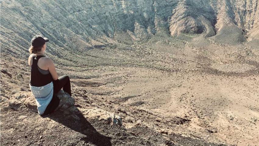 Frau blickt in Vulkankrater Caldera Blanca Lanzarote